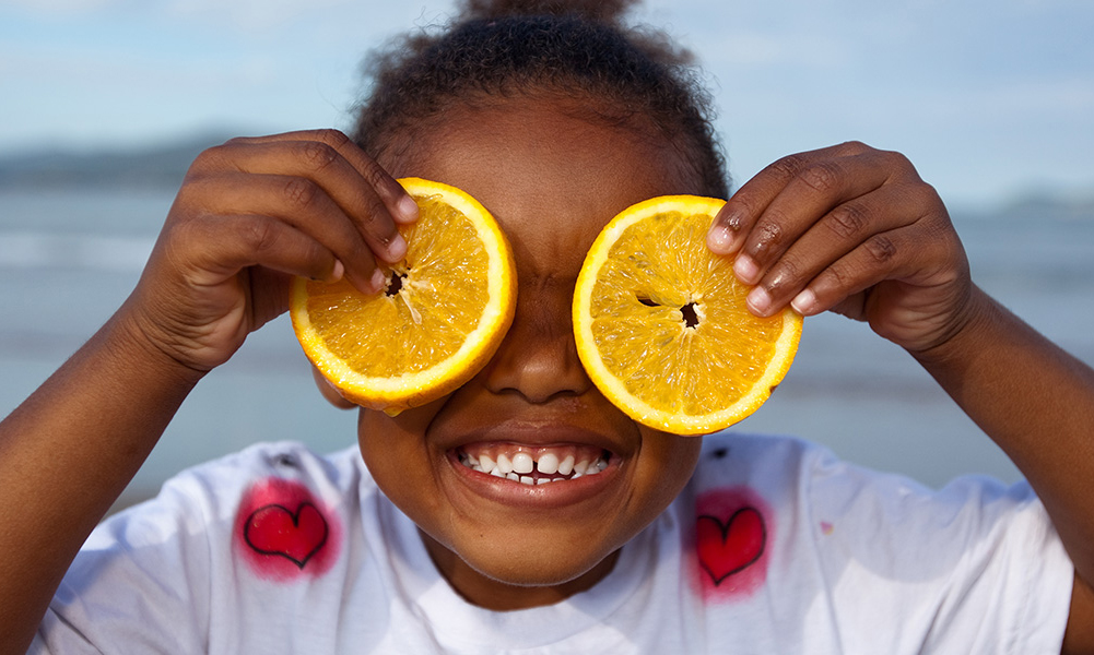 Young smiling girl holding oranges as eyes